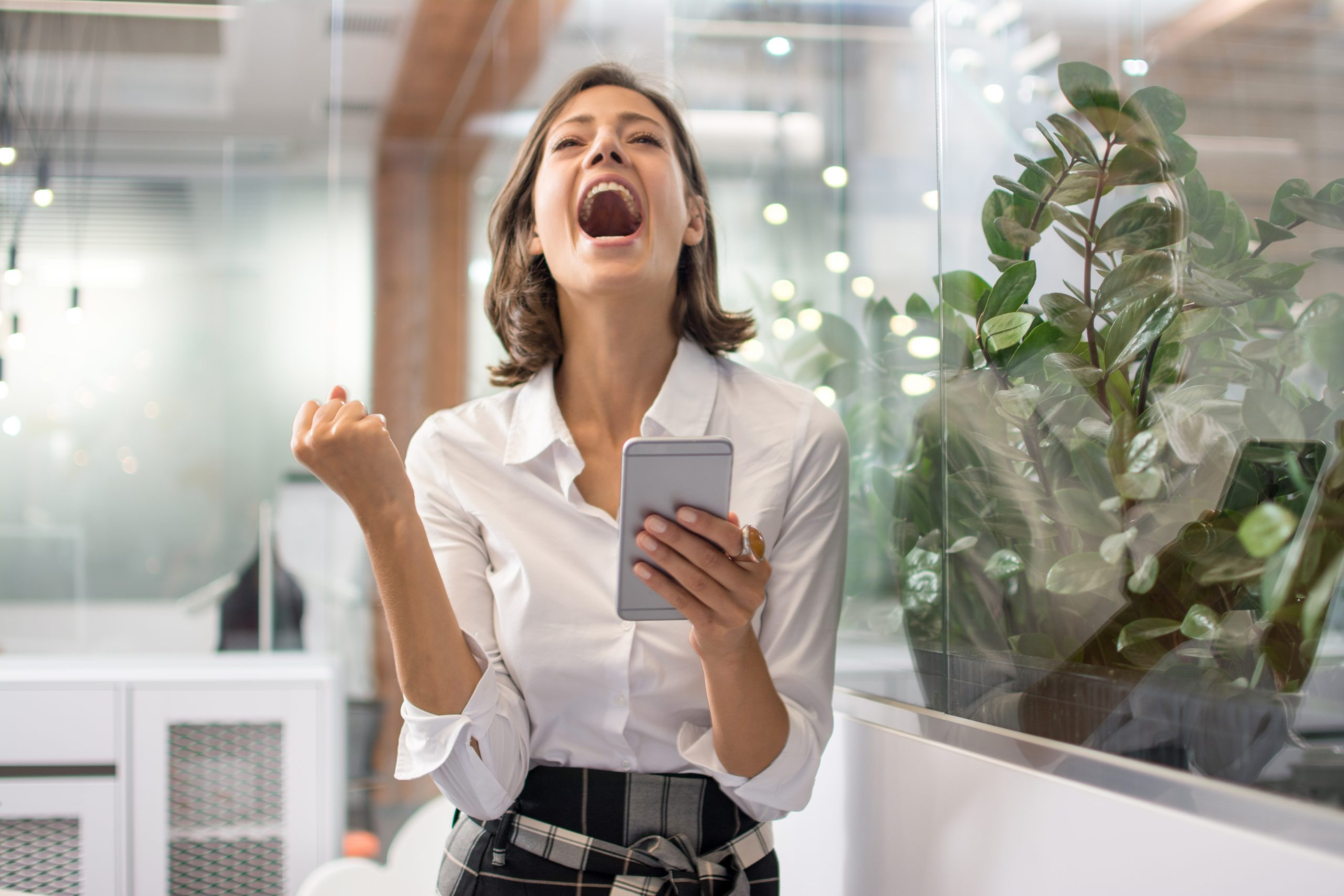 Excited cheerful young business woman with fist up receiving good news on smart phone and screaming in office
