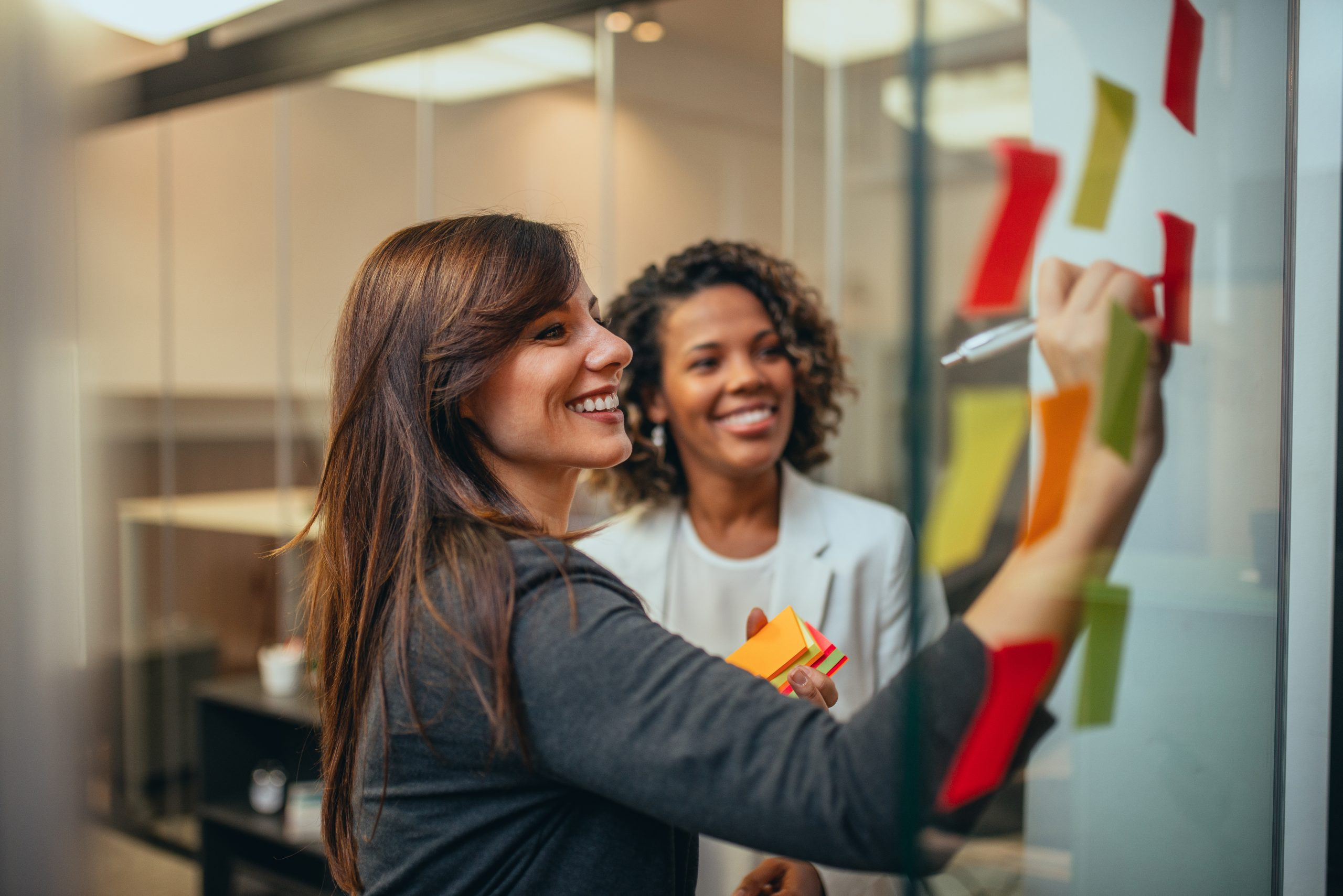 Smiling businesswoman brainstorming with adhesive notes on a glass wall in the office, portrait.