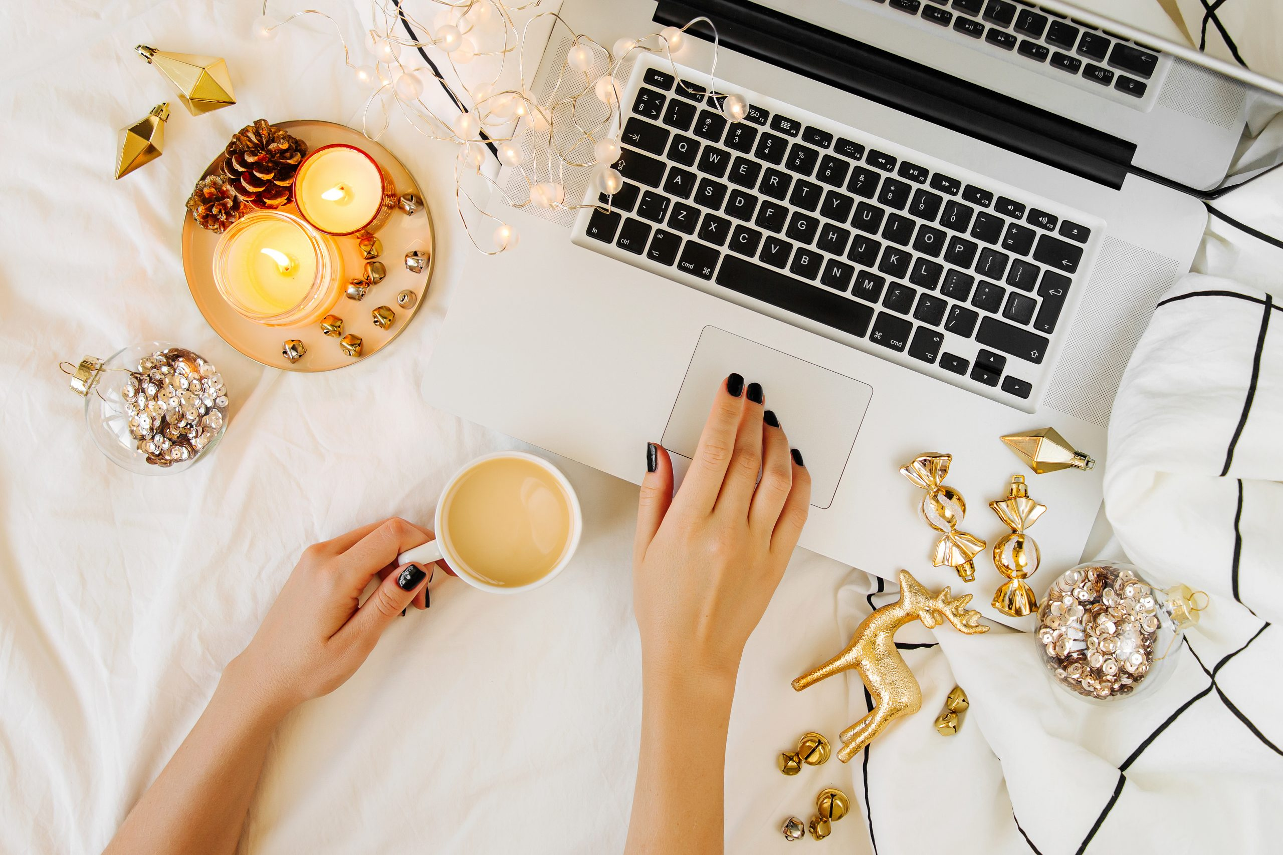 Christmas online shopping.  Woman has coffee, buys presents online. Laptop with Christmas decorations on white bed with a blanket. Holiday concept. Flat lay, top view