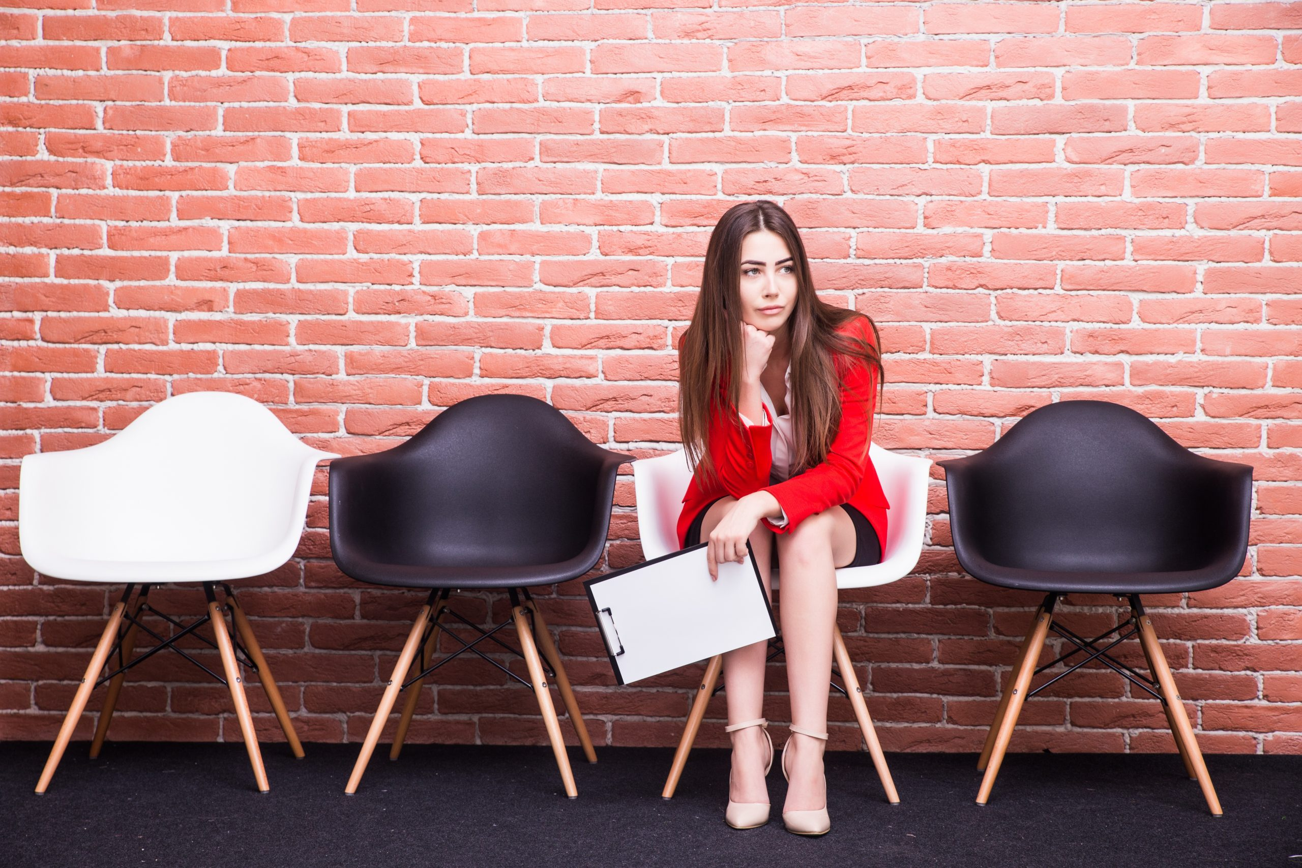 Bored young businesswoman holding paper and looking away while sitting on chair against grey background