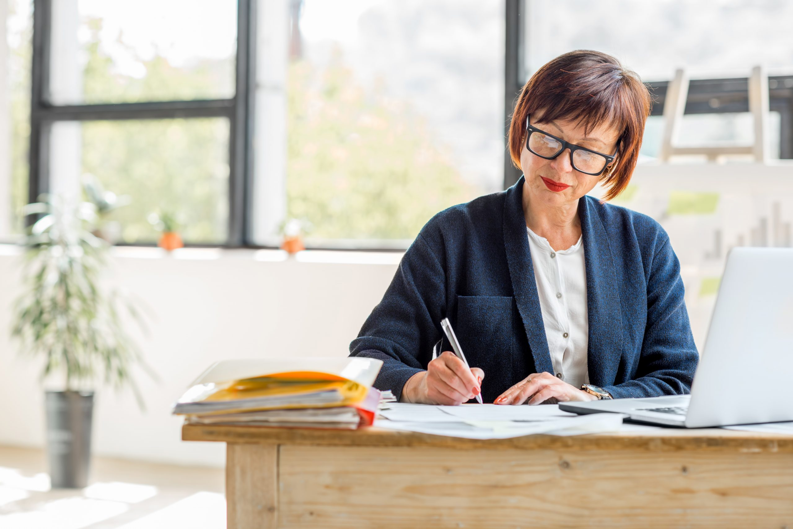 Senior businesswoman working with documents and laptop at the bright modern office interior
