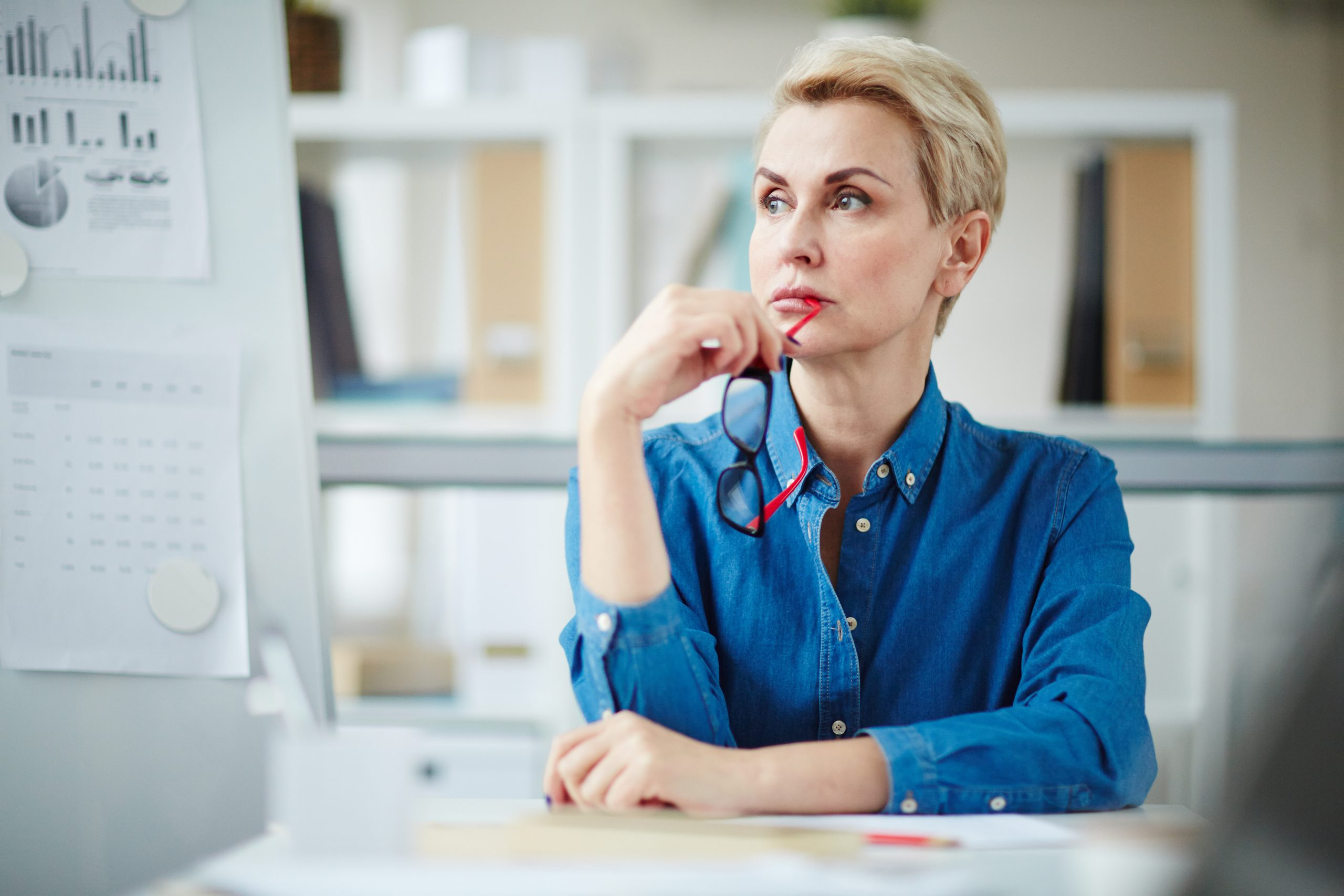 Serious mature teacher with eyeglasses thinking of working questions at workplace