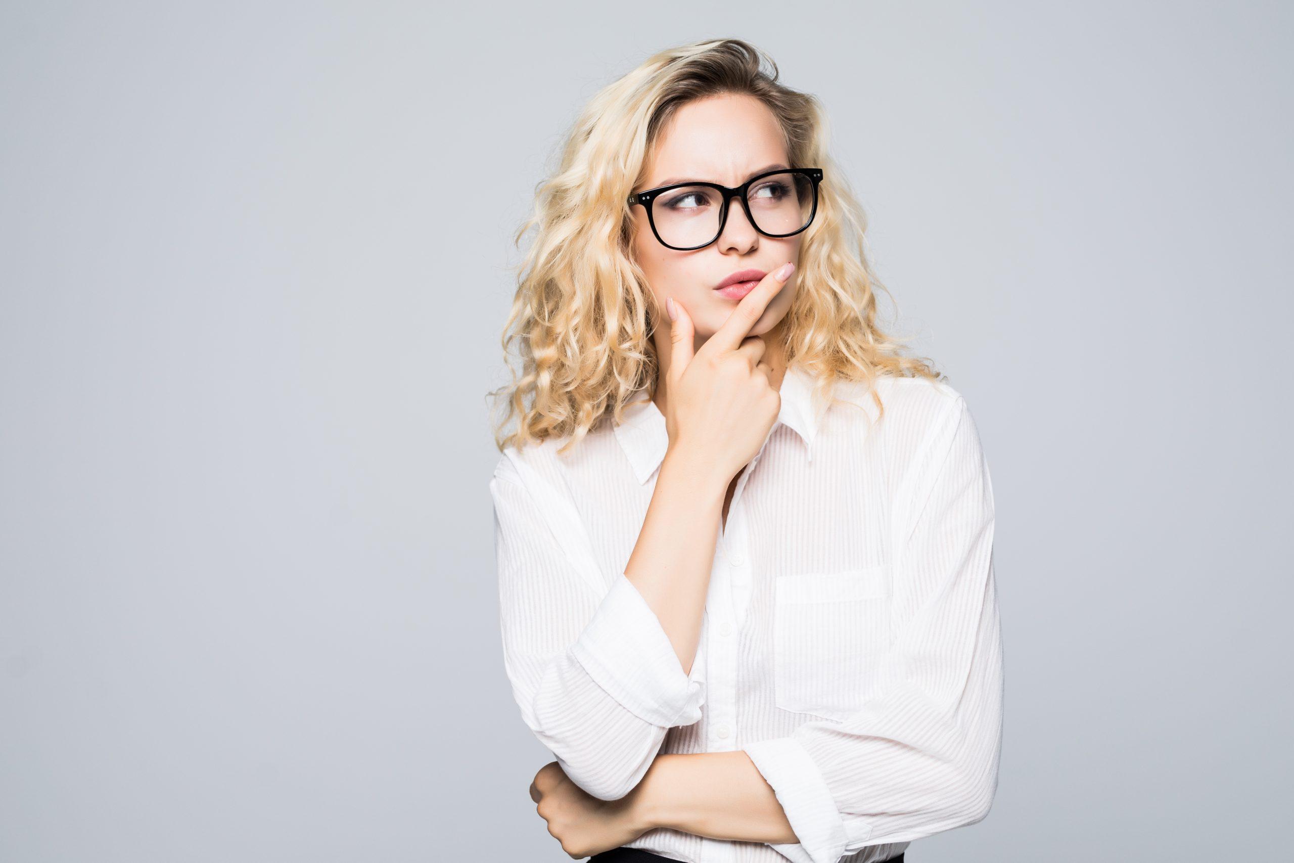 Beautiful thinking business woman isolated white background